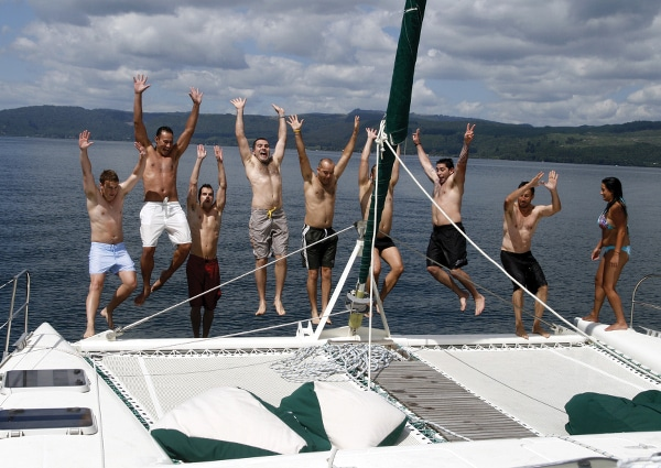 A group of exciting gay men jumping on the yacht